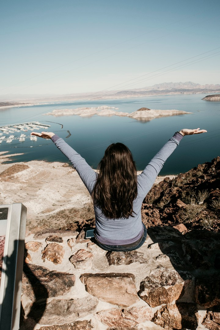A picture of a woman sitting on top of a wall at a panoramic view of Lake Mead Nevada