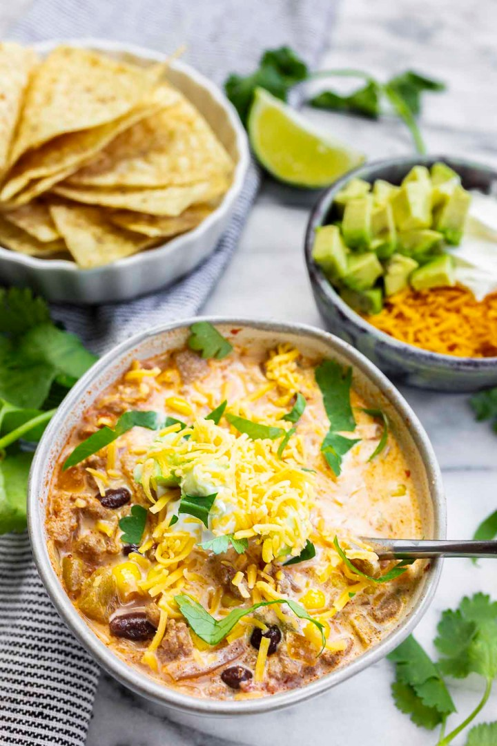 Creamy Turkey Taco Soup Recipe served with tortilla chips, avocado, cheese and sour cream