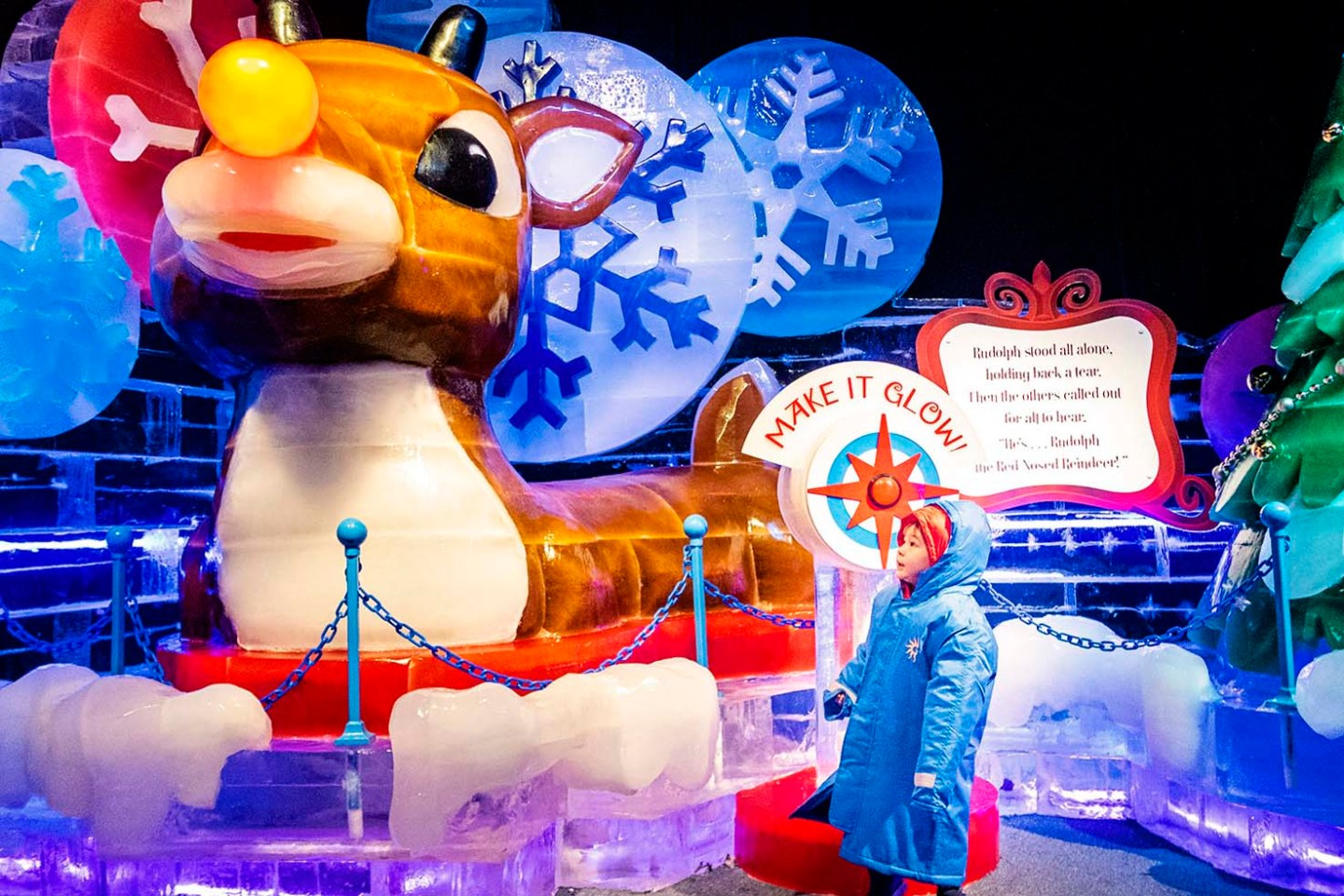 Toddler stands in awe of the huge Rudolph the Red Nose Reindeer ice sculpture At ICE! at the Gaylord Rockies Resort in Colorado