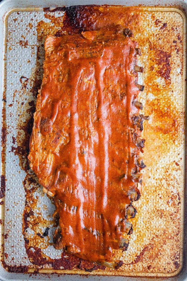Rack of ribs with homemade barbecue sauce on a baking sheet