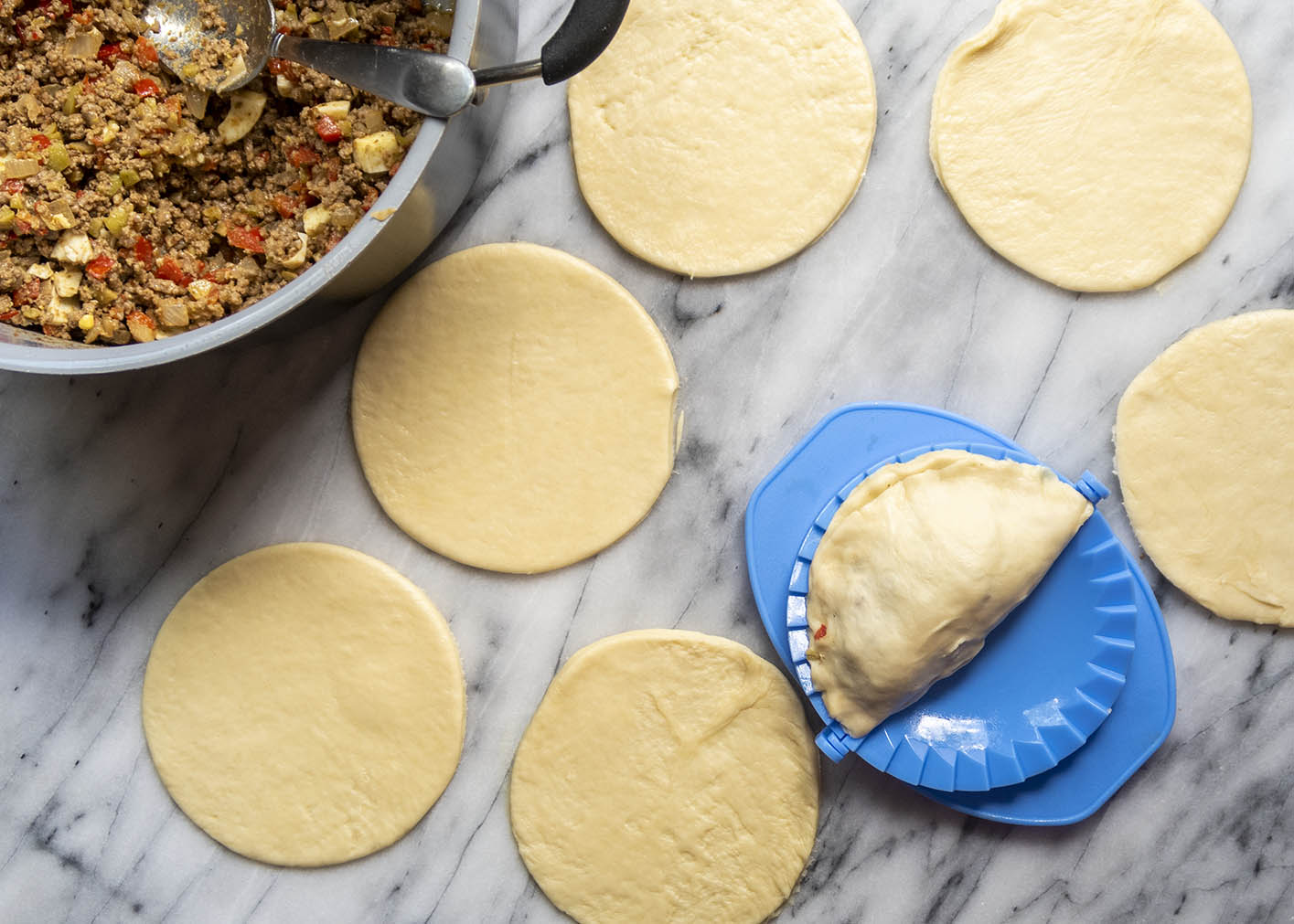 Assembling empanadas with fresh dough and meat filling