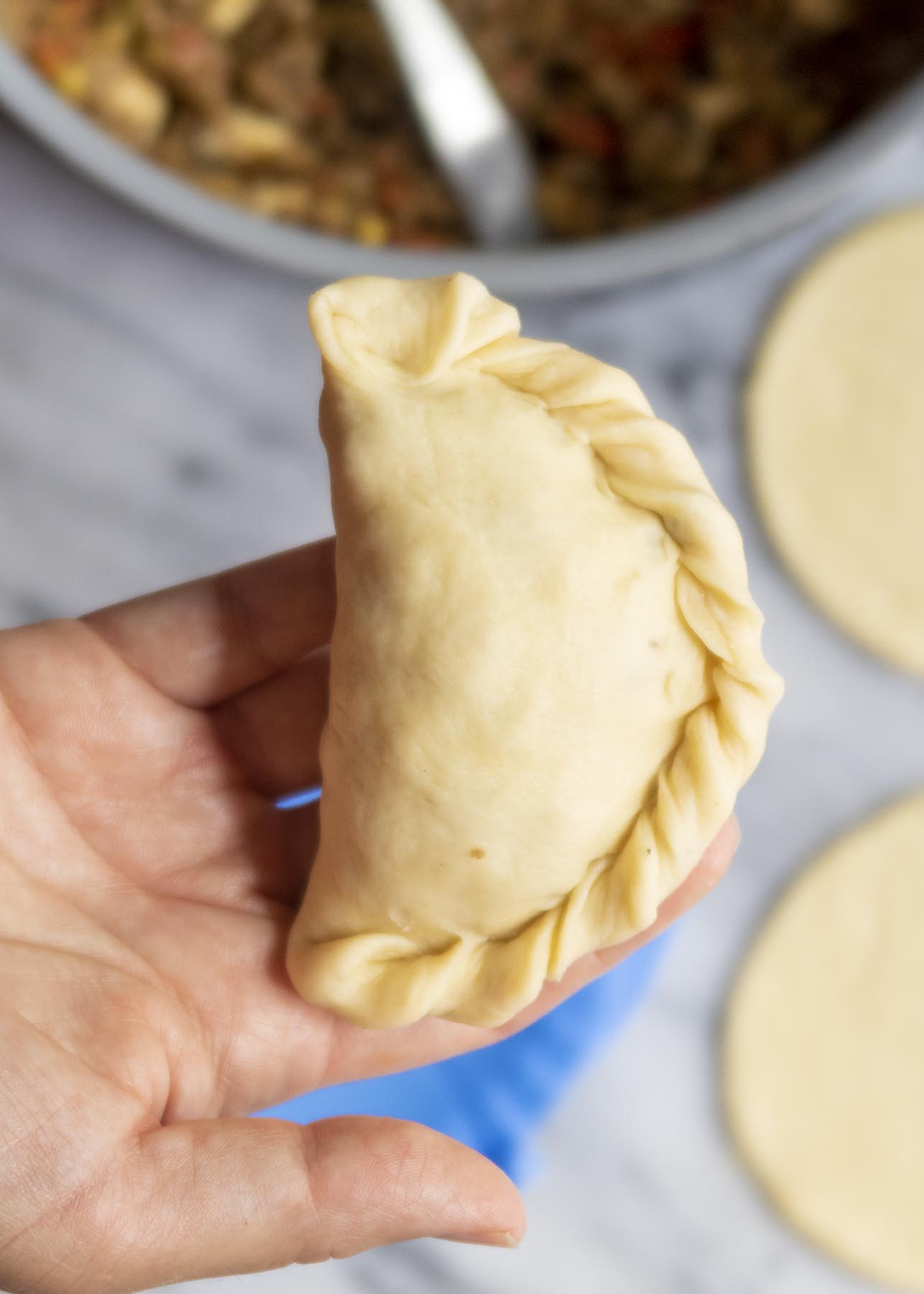 An unbaked homemade empanada displayed on person's hand to show roped edge