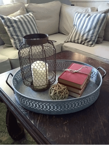 grouping of a rusted lantern, old books, and a ball of twine in a galvanized tray