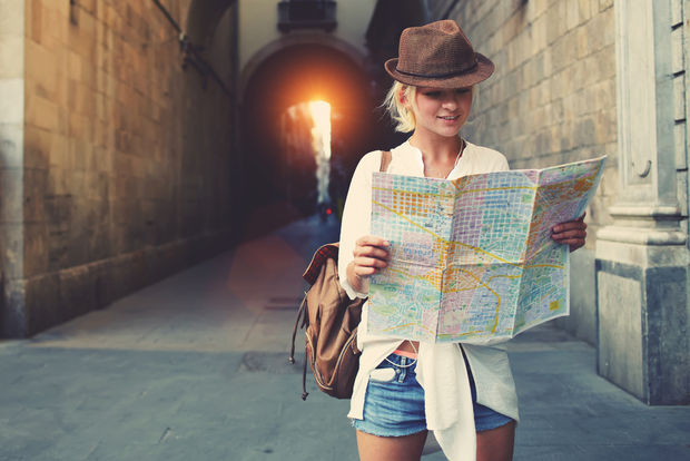 A woman is looking at a map while traveling abroad. (Shutterstock)