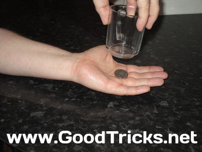 Image showing coin being held in center of your palm and below the glass.