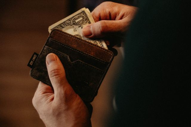 pulling dollar out of wallet