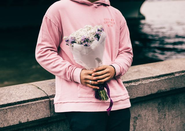 Woman holding flowers in pink sweater