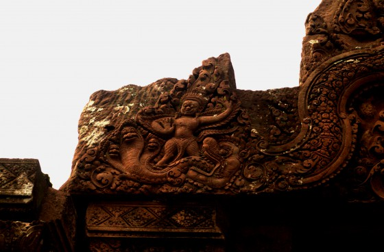 A naga motif from one of the Angkorean temples in Cambodia we visited in 2012. The three-headed naga seems to be hanging out with an apsara: the temples at Angkor are full of both such figures.