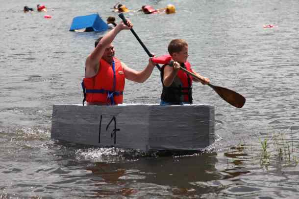 Two boys paddle a cardboard boat in the waters around Gore Bay.