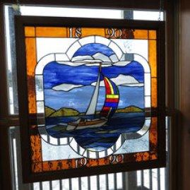 Blue stained glass window depiicting sailboat.