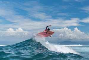 black surfer practicing extreme sport above ocean wave