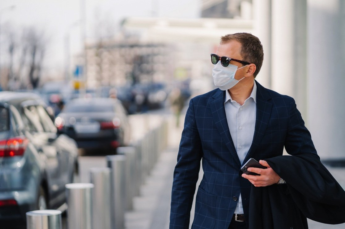 man on sidewalk wearing a mask