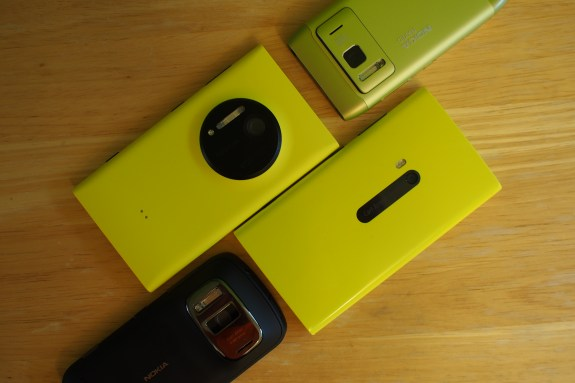 The evolution of Nokia's excellent camera experience on smartphones with the Nokia N8 (Symbian) in green, the black Nokia 808 PureView (41-megapixel Symbian phone), the Lumia 920 (bottom right in glossy yellow), and the Lumia 1020 (upper left in matte yellow)