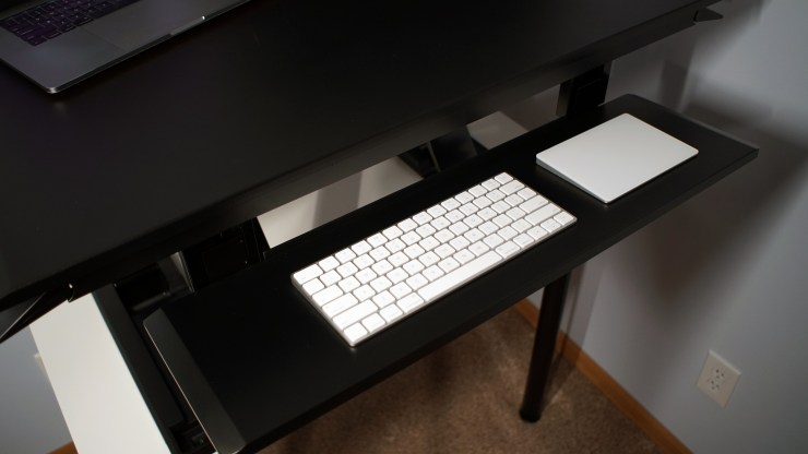 The keyboard tray adjusts independently and includes a negative tilt option.