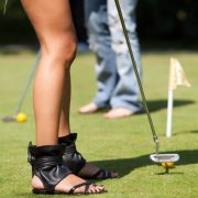 Image of woman golfer wearing cutoffs and sandals