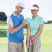 Man coaching woman golfer