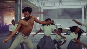 "Donald Glover doing the famous ""Gwara Gwara"" dance with children dressed in school uniform as his background dancers"