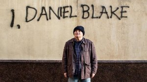 Solitary man stands in front of wall spray painted with I, Daniel Blake