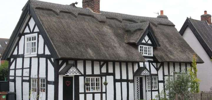 Big old black and white house with thatched roof