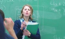 Teacher in front of green board with equations on