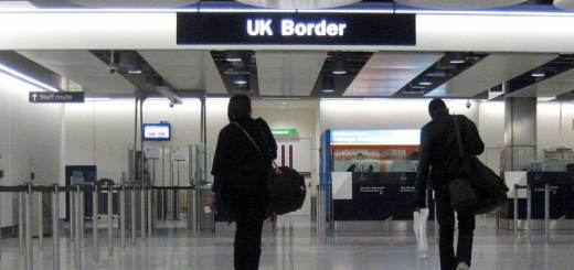 Two people at Heathrow walking to UK Border sign