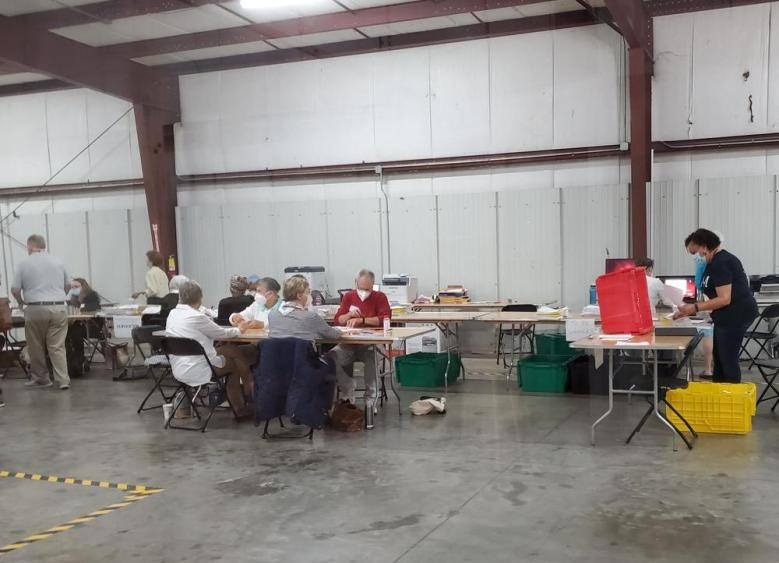 workers tabulate absentee ballots in a warehouse