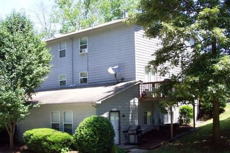 gray fourplex apartment complex with mature landscaping and satellite dish