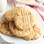 Peanut Butter Cookies piled on a white plate with a red towel in the background.