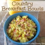 Diced ham, potatoes, peppers, and scrambled eggs in a blue bowl. With a glass of orange jucie in the background.