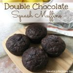 Double Chocolate Squash Muffins on a wooden cutting board.