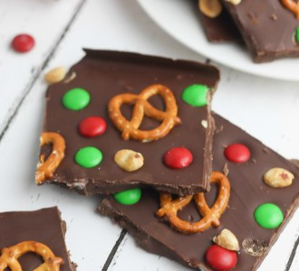 Chocolate christmas bark on a baking sheet with pretzels, peanuts and candies.