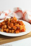 Oven-roasted sweet potatoes and bacon on a white plate.