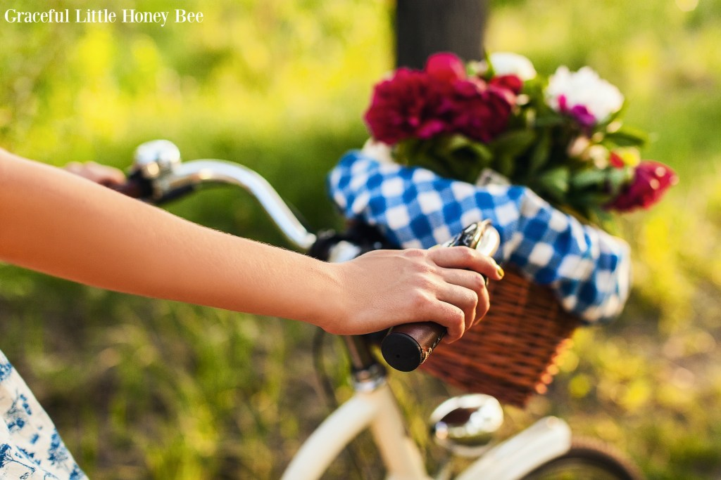 A basket full of colorful flowers on the front of a white bicycle.