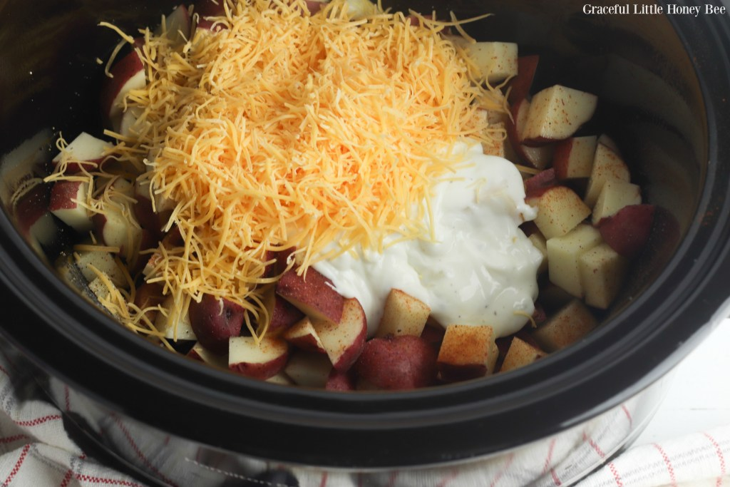 Potaotes, cheese and sour cream in a slow cooker.