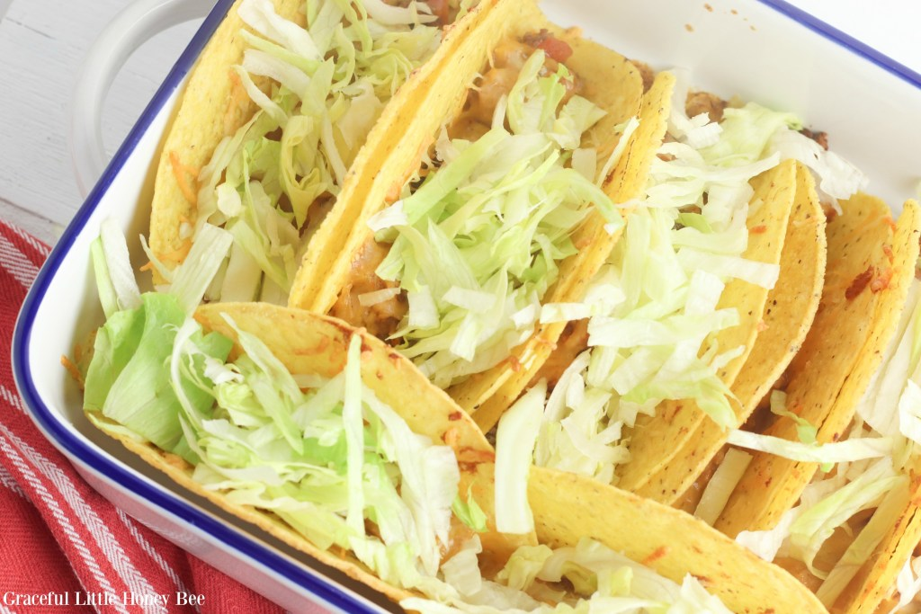 Finished tacos topped with lettuce in baking dish.