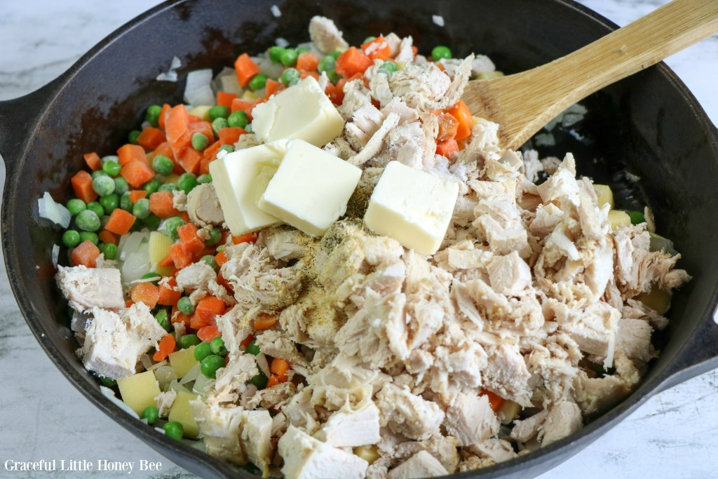 Mixed vegetables, cooked turkey and butter in a cast iron skillet.