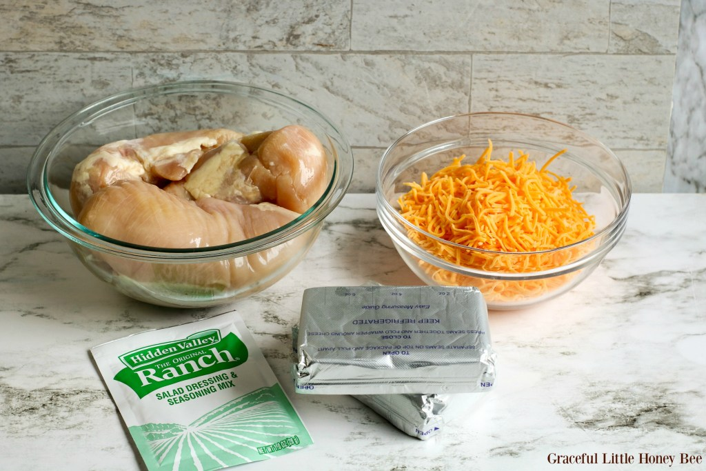 Ingredients sitting on a marble countertop including, raw chicken breast, shredded cheddar cheese, cream cheese and ranch dressing powder.