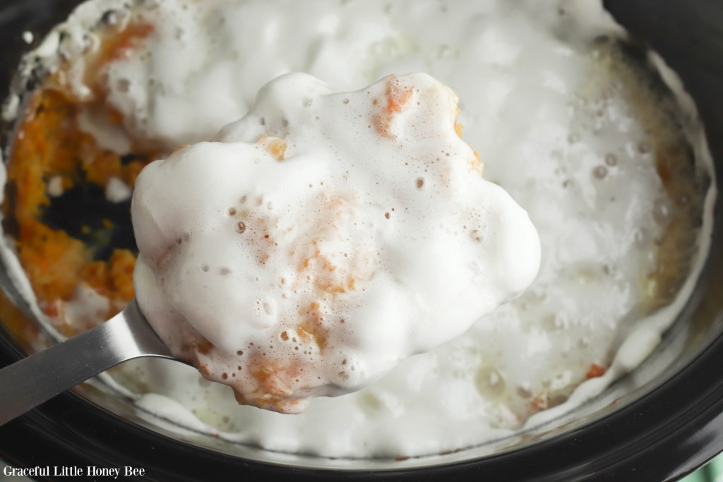 Cooked Sweet Potato Casserole with melted marshmallows on top in black slow cooker.