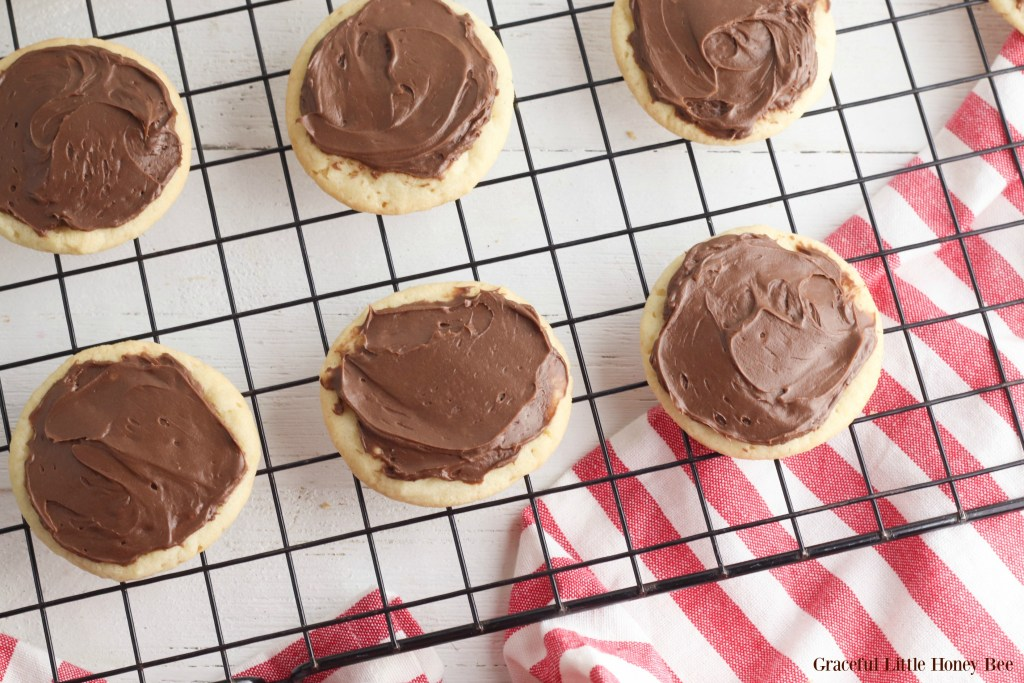 Sugar cookies with chocolate frosting sitting on a cooling rack.