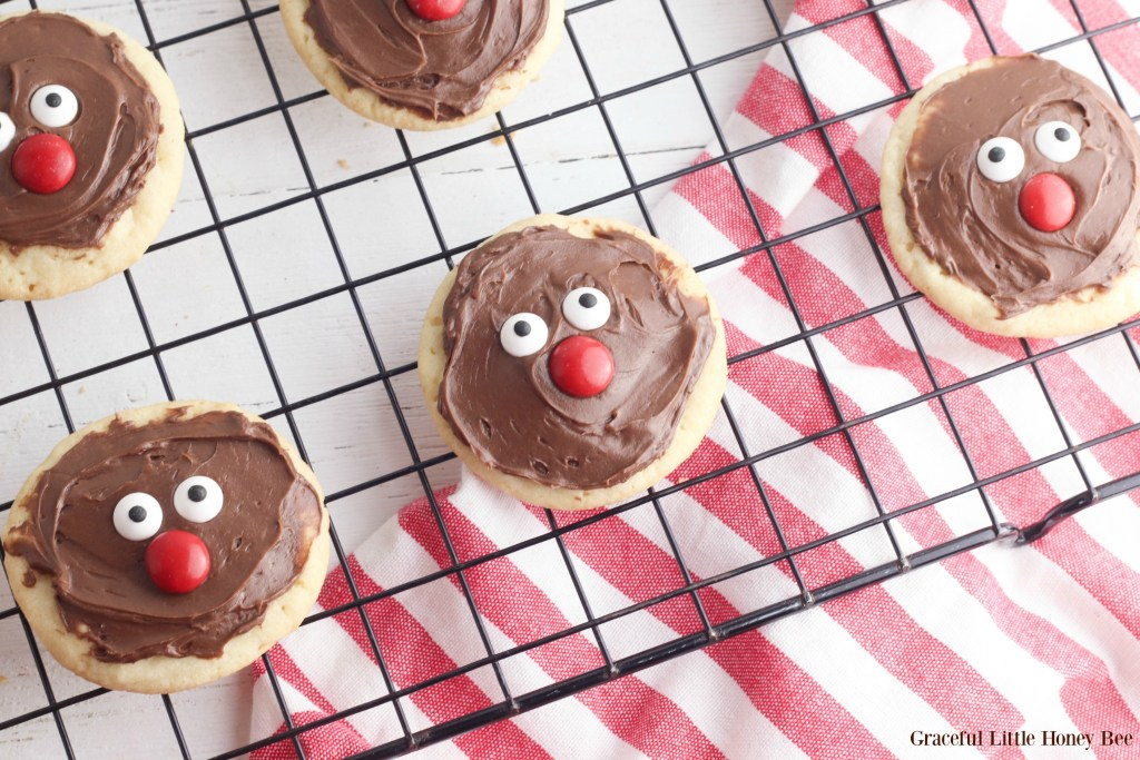 Sugar cookies with chocolate frosting, candy eyes and nose sitting on a wire cooling rack.