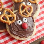A sugar cookie with chocolate frosting, candy eyes, nose and pretzel ears that makes it look like a reindeer.