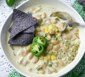 Chicken Enchilada Soup in a white bowl topped with blue corn tortilla chips and fresh slices of jalapenos.