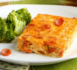 A slice of the Pepperoni Pizza Casserole sitting next to steamed broccoli on a white plate.