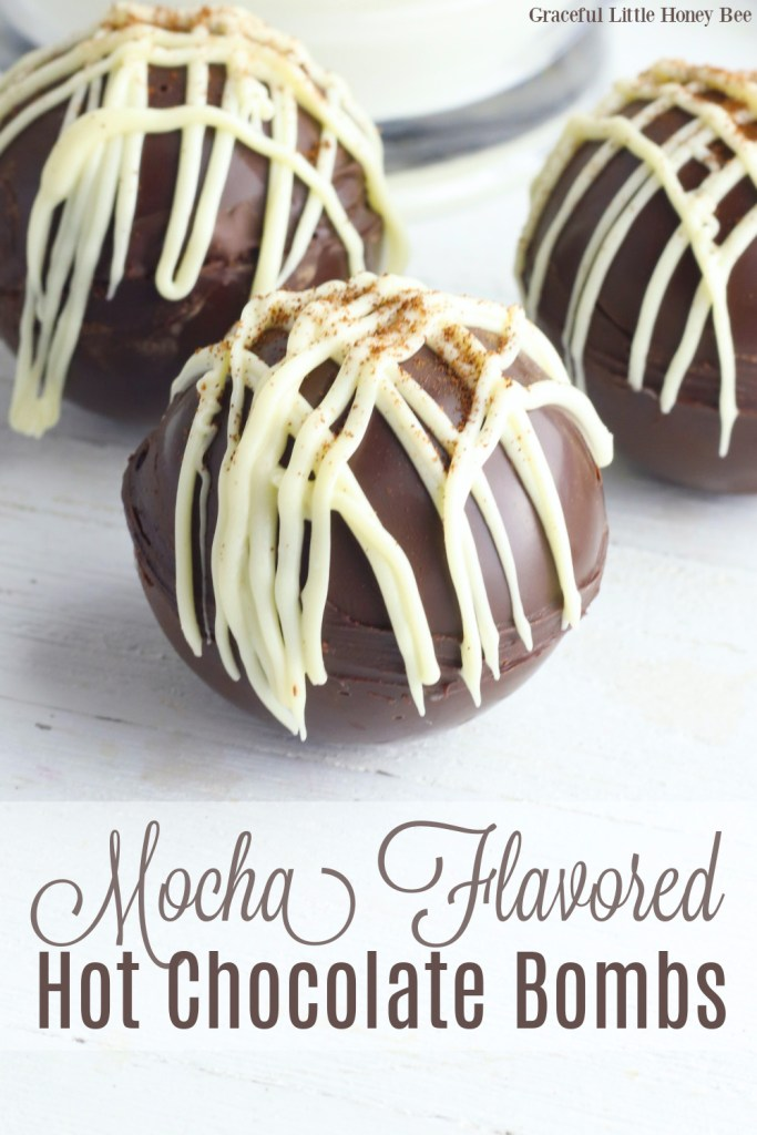 Mocha Hot Chocolate Bombs drizzled with white chocolate candy coating, sitting on a white countertop.