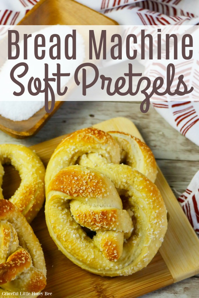 Four soft pretzels sitting on a cutting board.