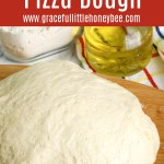 Pizza dough sitting on a wooden cutting board.