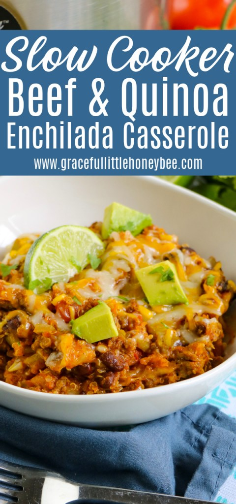 Quinoa Enchilada Casserole in a white bowl topped with cheese and garnished with lime.
