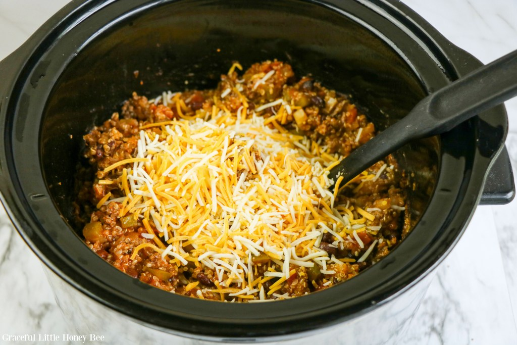 Enchilada casserole with shredded cheese added before mixing it in.