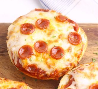 Pizza Bagel sitting on a wooden cutting board.