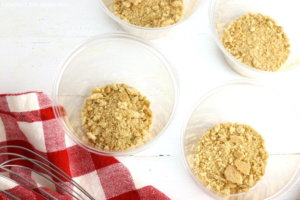 Graham cracker crumbs in clear plastic cups.